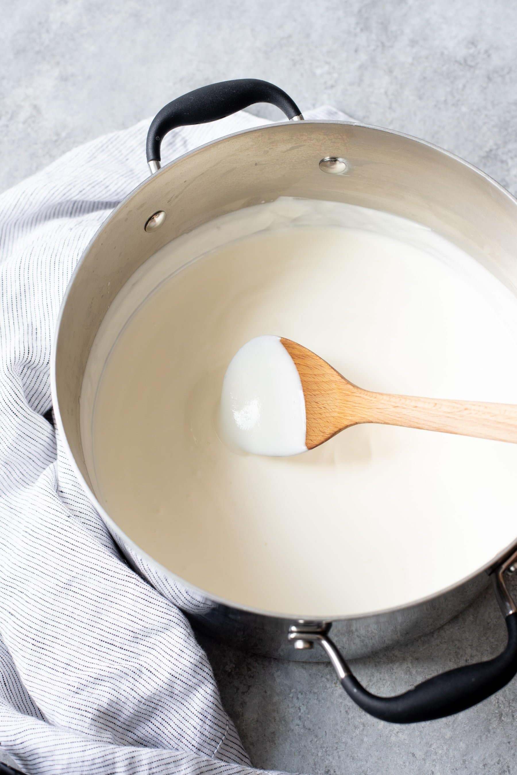 Wooden spoon stirring homemade yogurt in a soup pot