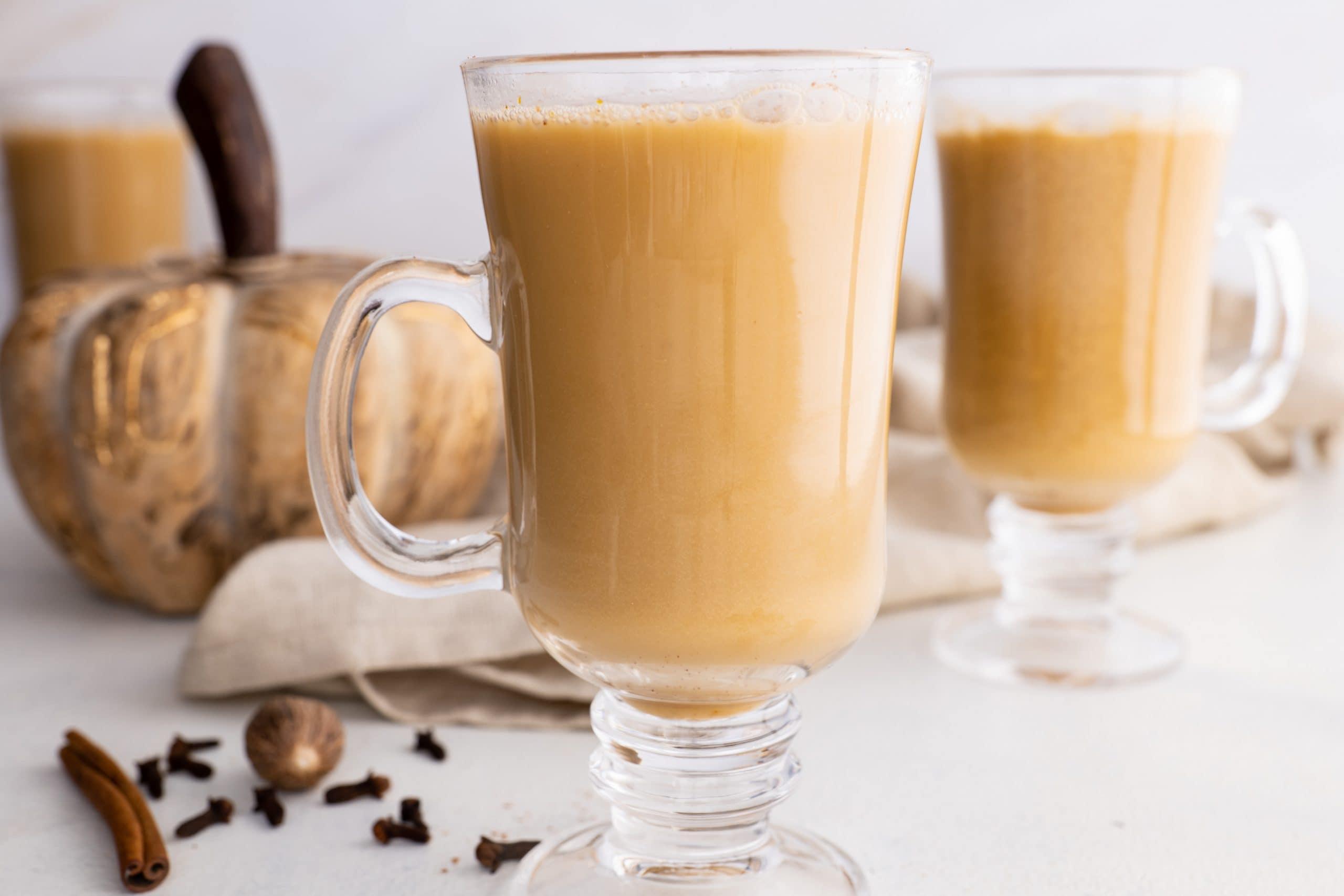 A homemade pumpkin spice latte shows through a tall glass mug. A wooden pumpkin is in the background.
