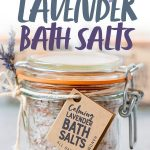 "Three glass jars of Calming Lavender Bath Salts with gift tags and sprigs of lavender. Text overlay reads ""Calming Lavender Bath Salts."""