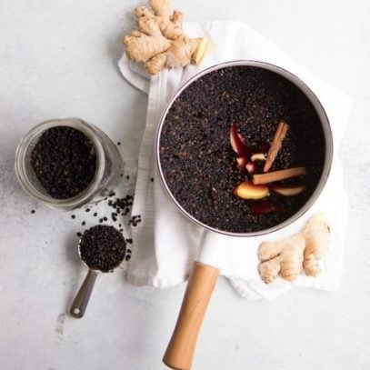 Elderberries sit in a wooden handled pot, surrounded by other ingredients for elderberry syrup.