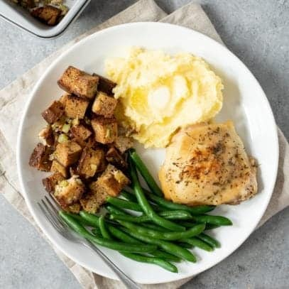 Overhead shot of a white plate containing grain-free Thanksgiving stuffing, green beans, mashed potatoes, and poultry