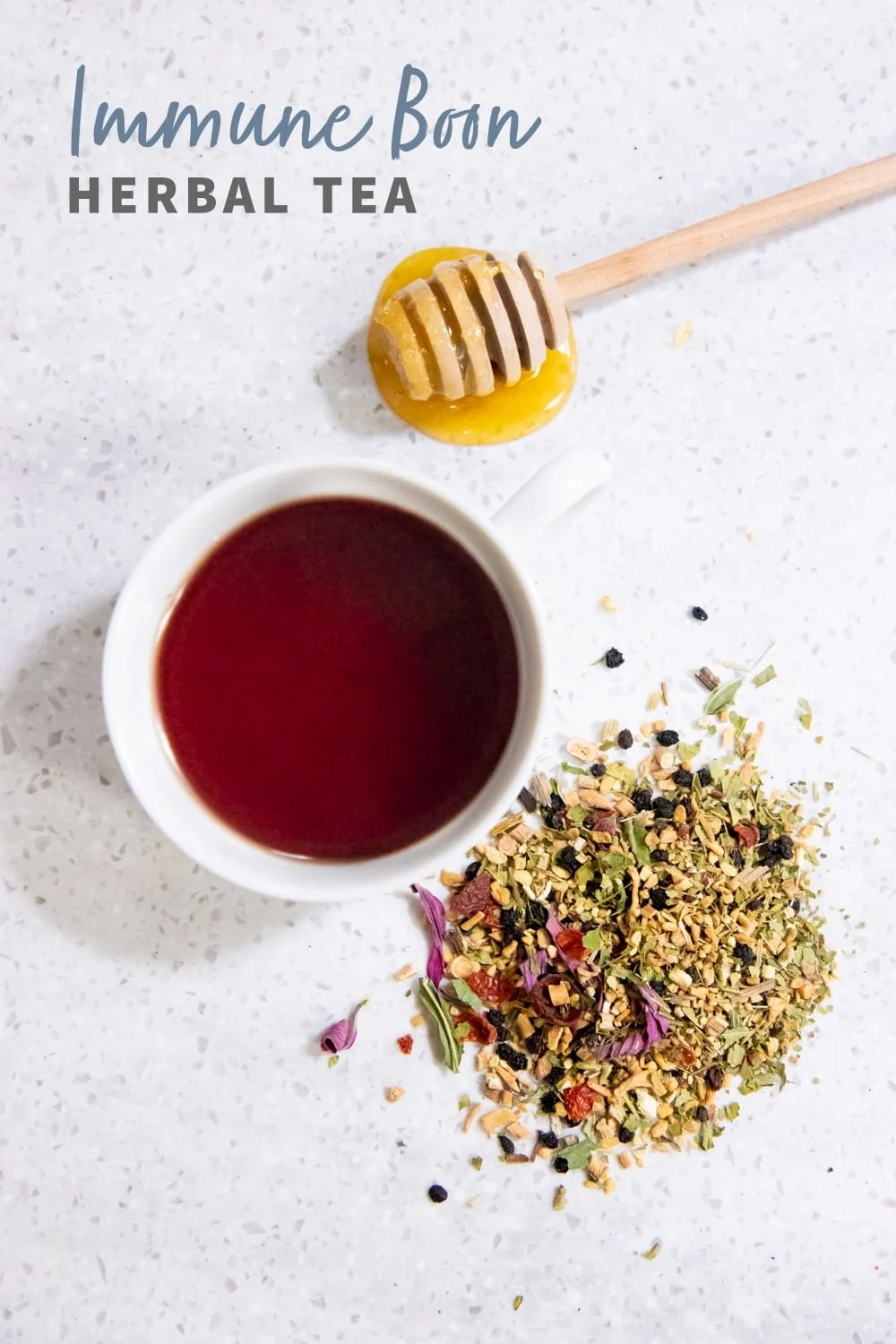 "Overhead shot of tea in a white teacup, with herbs and a honey dipper nearby. Text overlay reads ""Immune Boon Herbal Tea."""