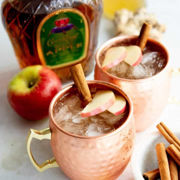 Autumn Apple Kombucha Whiskey Moscow Mule in hammered copper mugs with apple slices and a cinnamon stick floating on top, with the ingredients for the drink behind the cups.