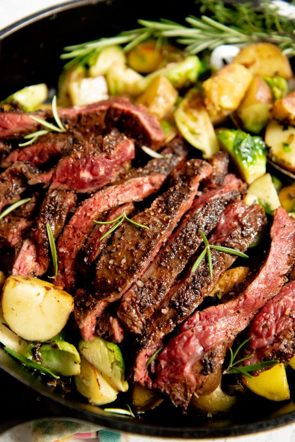 Sliced seared steak on top of Potatoes and Brussels sprouts in a cast iron skillet