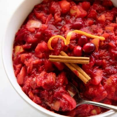 Spoon dipping into a white bowl of Chunky Cranberry Applesauce, topped with cinnamon sticks and citrus peels