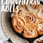 "Overhead of a cast iron skillet filled with make-ahead vegan cinnamon rolls drizzled with icing. A text overlay reads ""Vegan Cinnamon Rolls"""