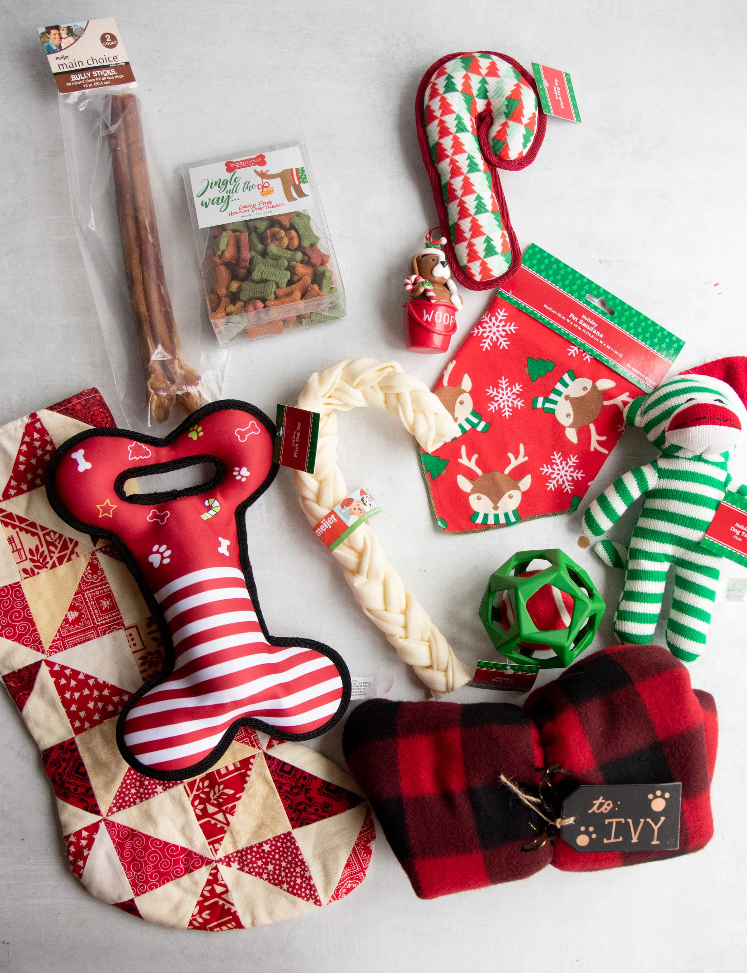 Stocking fillers for a dog - toys, treats, a red and white stocking, and a custom dog coat