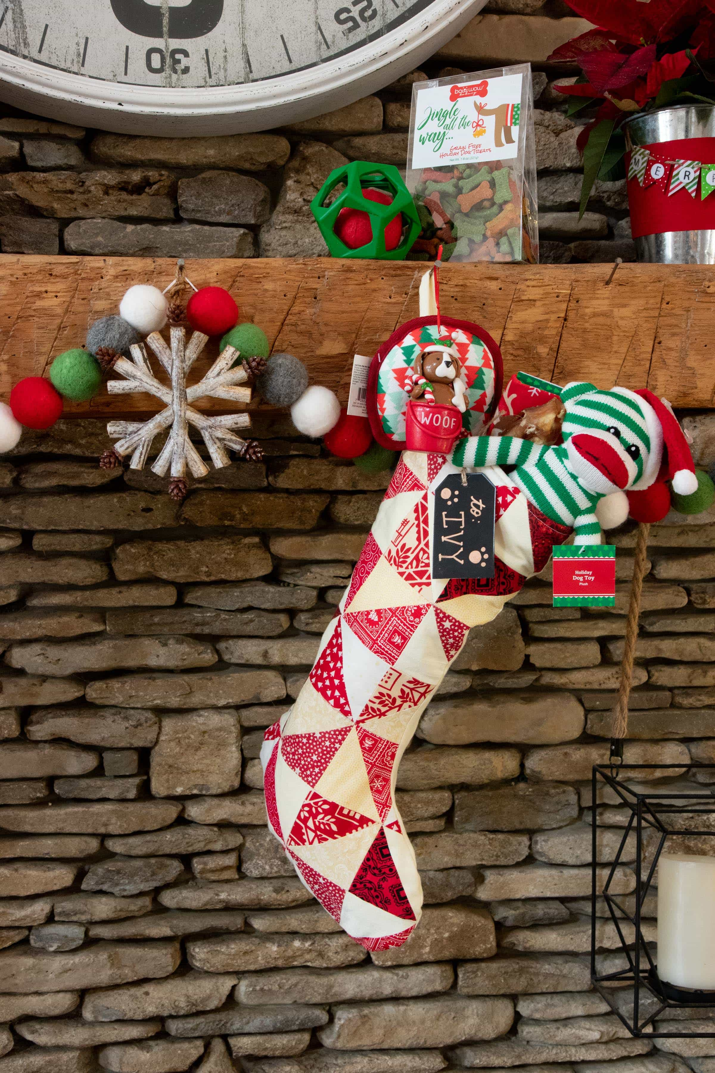 "Red and white stocking filled with dog treats and toys hung on a mantle and tagged with ""Ivy."""