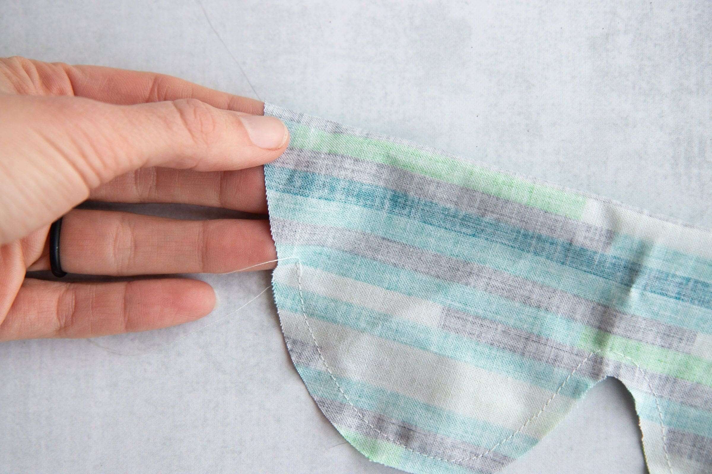 Hand holding fabric for a Soothing Headache Eye Mask that is mostly stitched but has an opening left