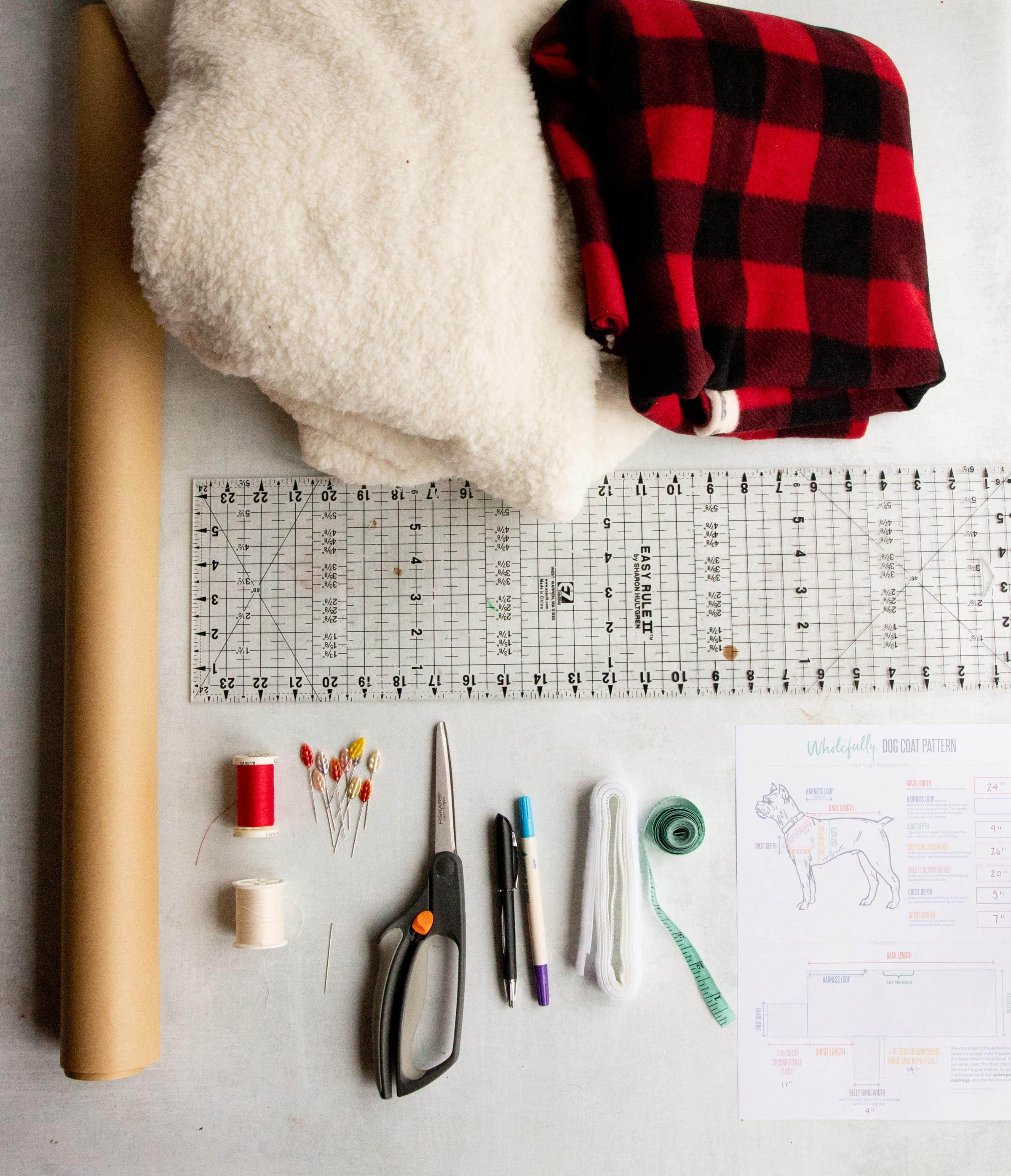 Materials laid out for a custom dog coat - fleece, faux fur, pattern paper, scissors, thread, pins, measuring tap, measurements sheet, and a ruler