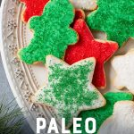 """Grain-Free Paleo Sugar Cookies with Coconut Butter Frosting and Christmas sprinkles on a white platter. A text overlay reads """"Paleo Sugar Cookies."""""""