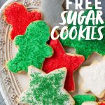 """Grain-Free Paleo Sugar Cookies with Coconut Butter Frosting and Christmas sprinkles on a white platter. A text overlay reads """"Grain Free Sugar Cookies."""""""