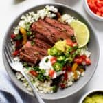 Steak Fajita Bowls with Cilantro-Lime Cauliflower Rice in a grey bowl on a white background, with toppings in individual bowls nearby