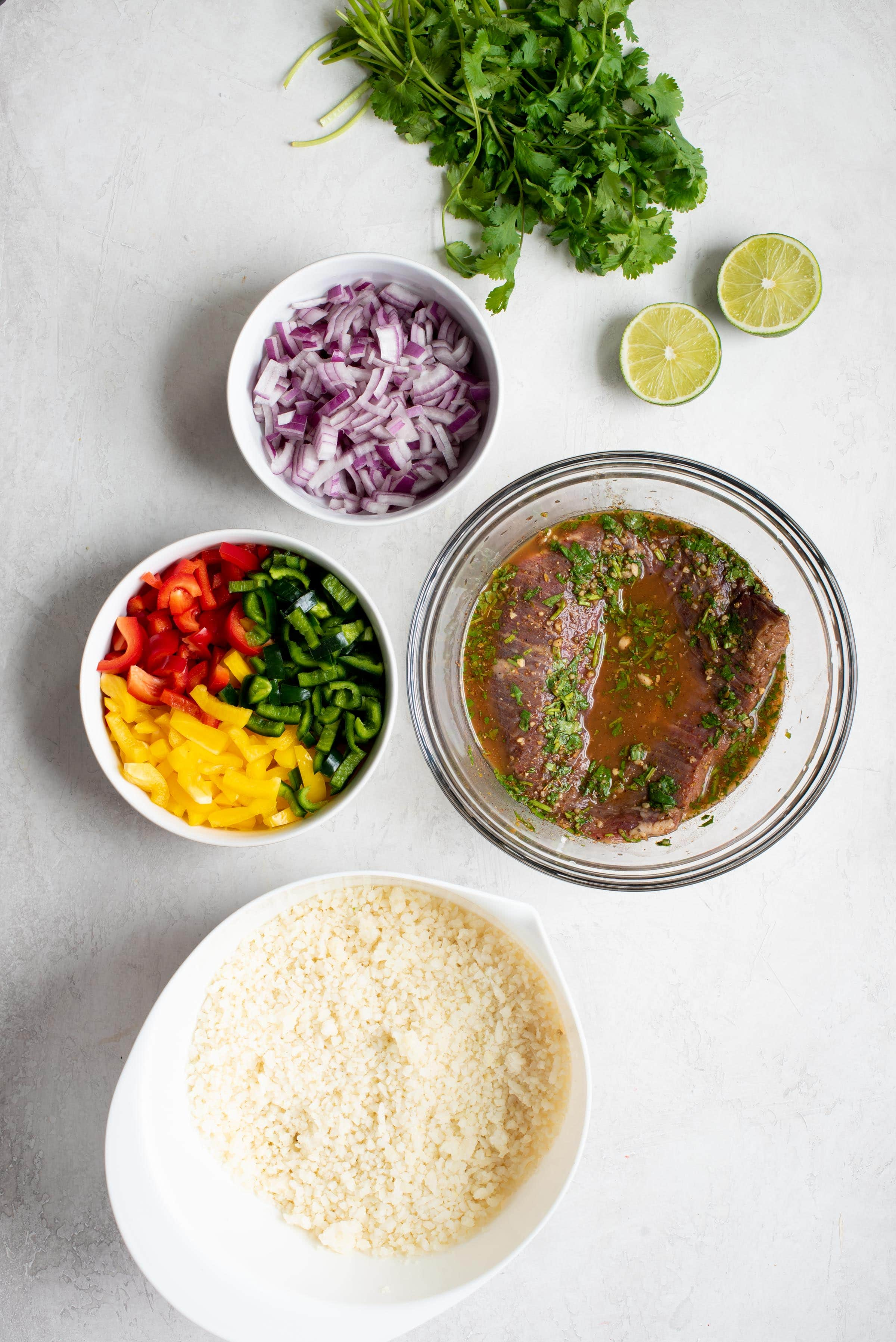 Ingredients for Steak Fajita Bowls with Cilantro-Lime Cauliflower Rice in individual bowls - marinating steak, peppers, onions, lime, cilantro, cauliflower rice