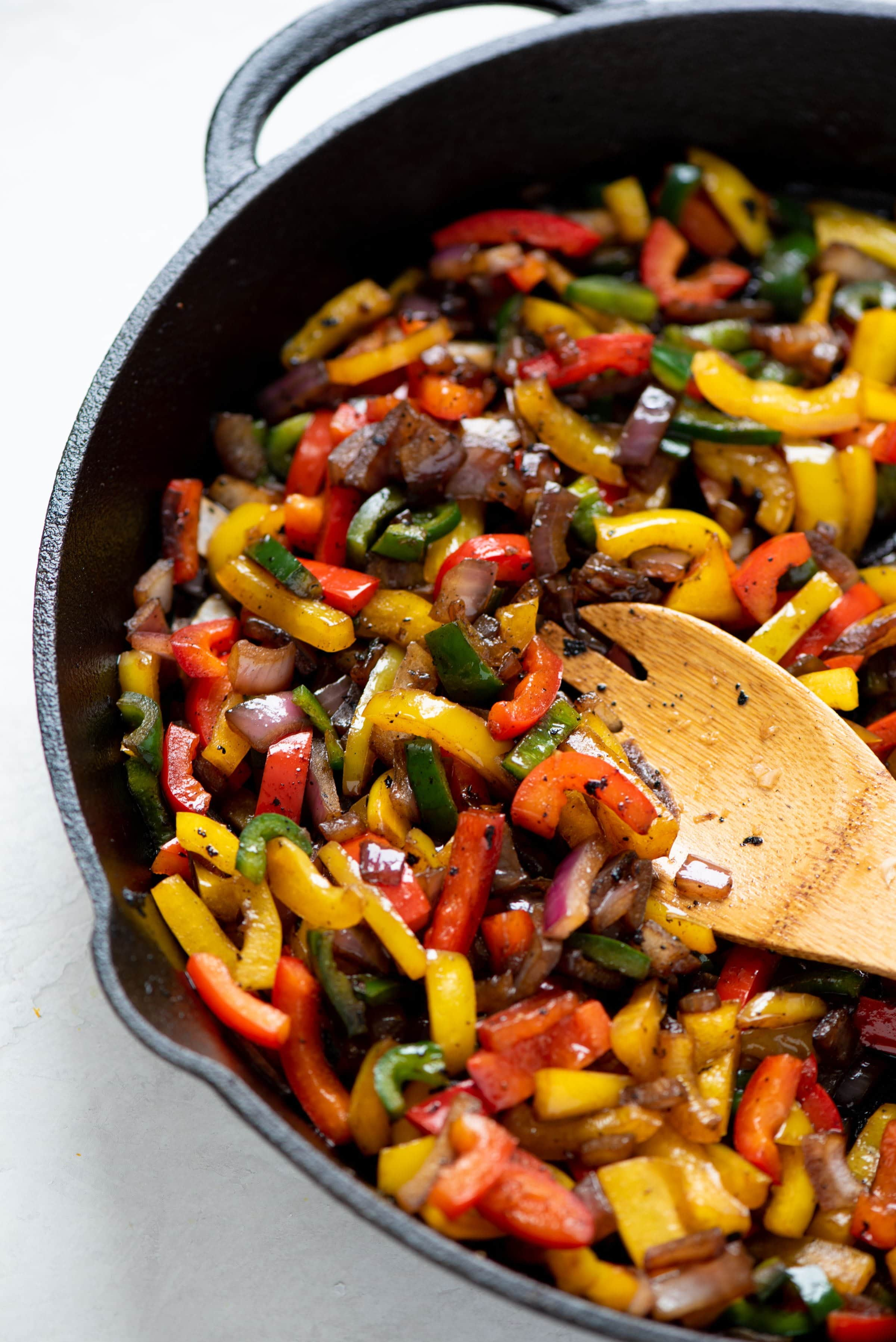 Sautéed peppers and onions in a cast iron skillet, being stirred with a wooden spoon