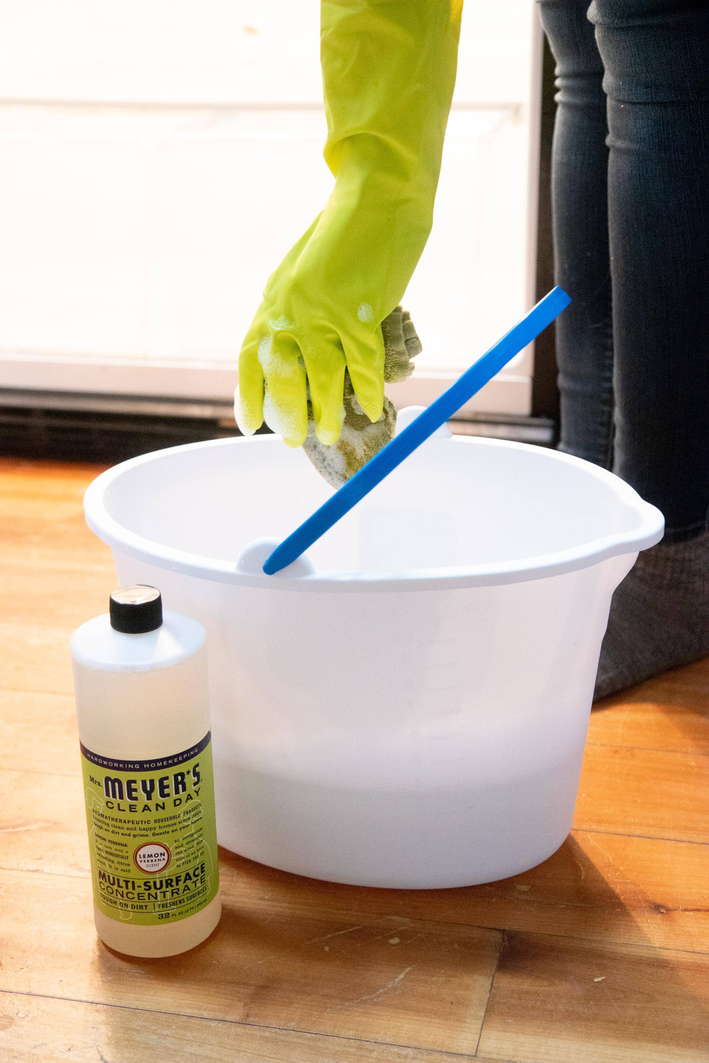 Hand in a lime green dish glove holding a soapy sponge above a mop bucket, with a bottle of Meyer's Clean Day all-purpose cleaner in front of it