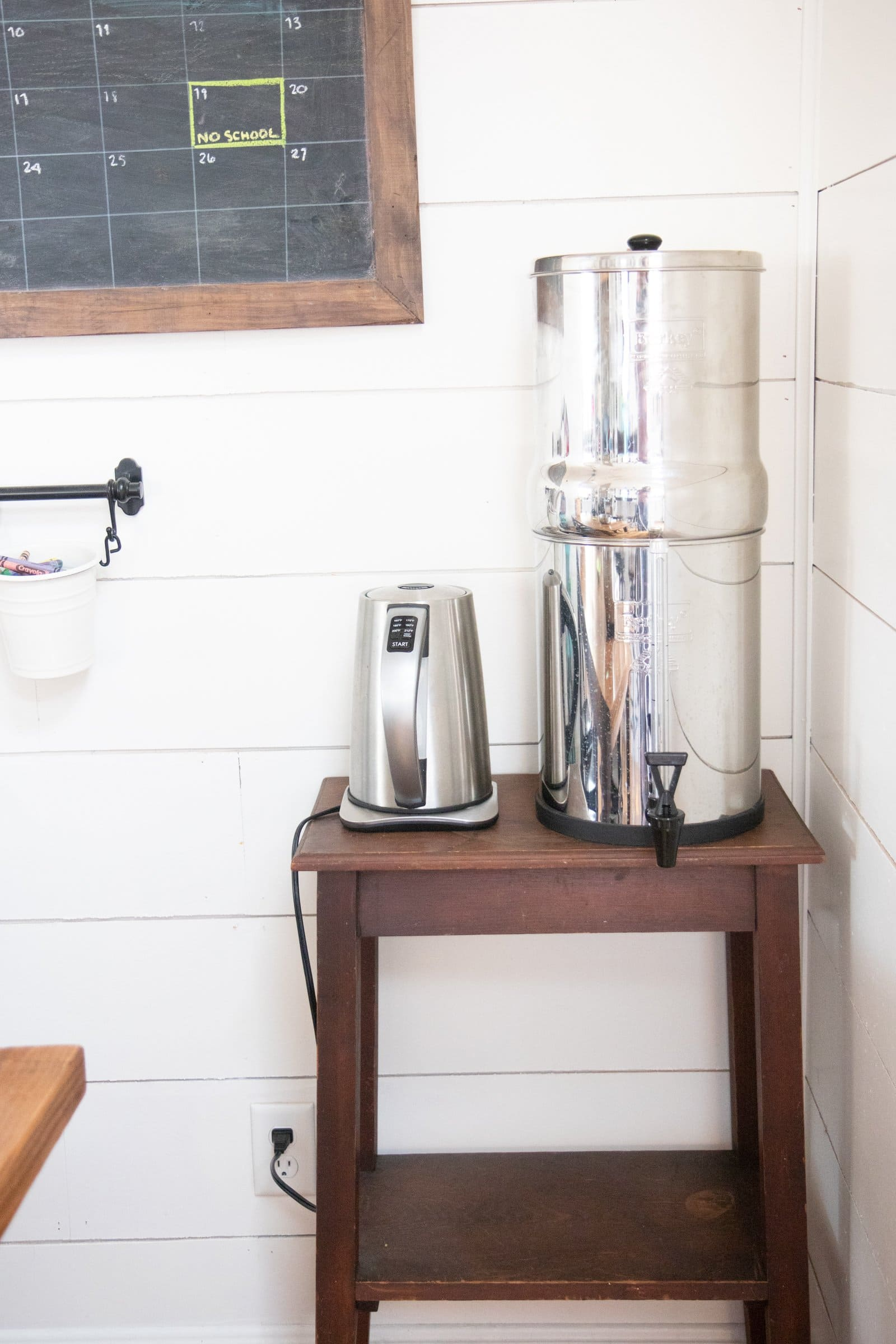 A stainless steel water filter next to an electric tea kettle on a small wooden table.