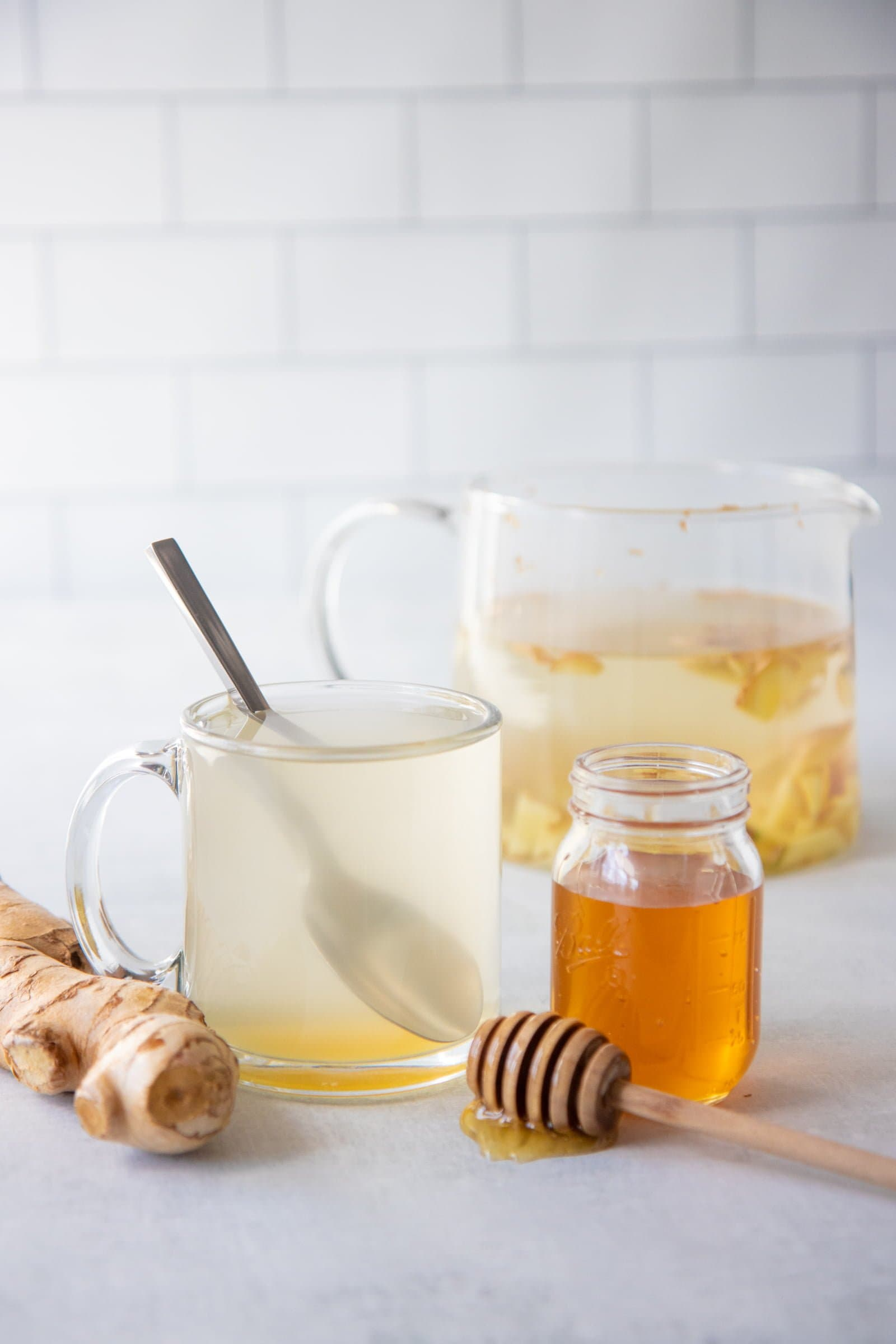 A clear mug of ginger tea with a spoonful of honey in it sits beside a jar of honey and a large glass pitcher of tea.