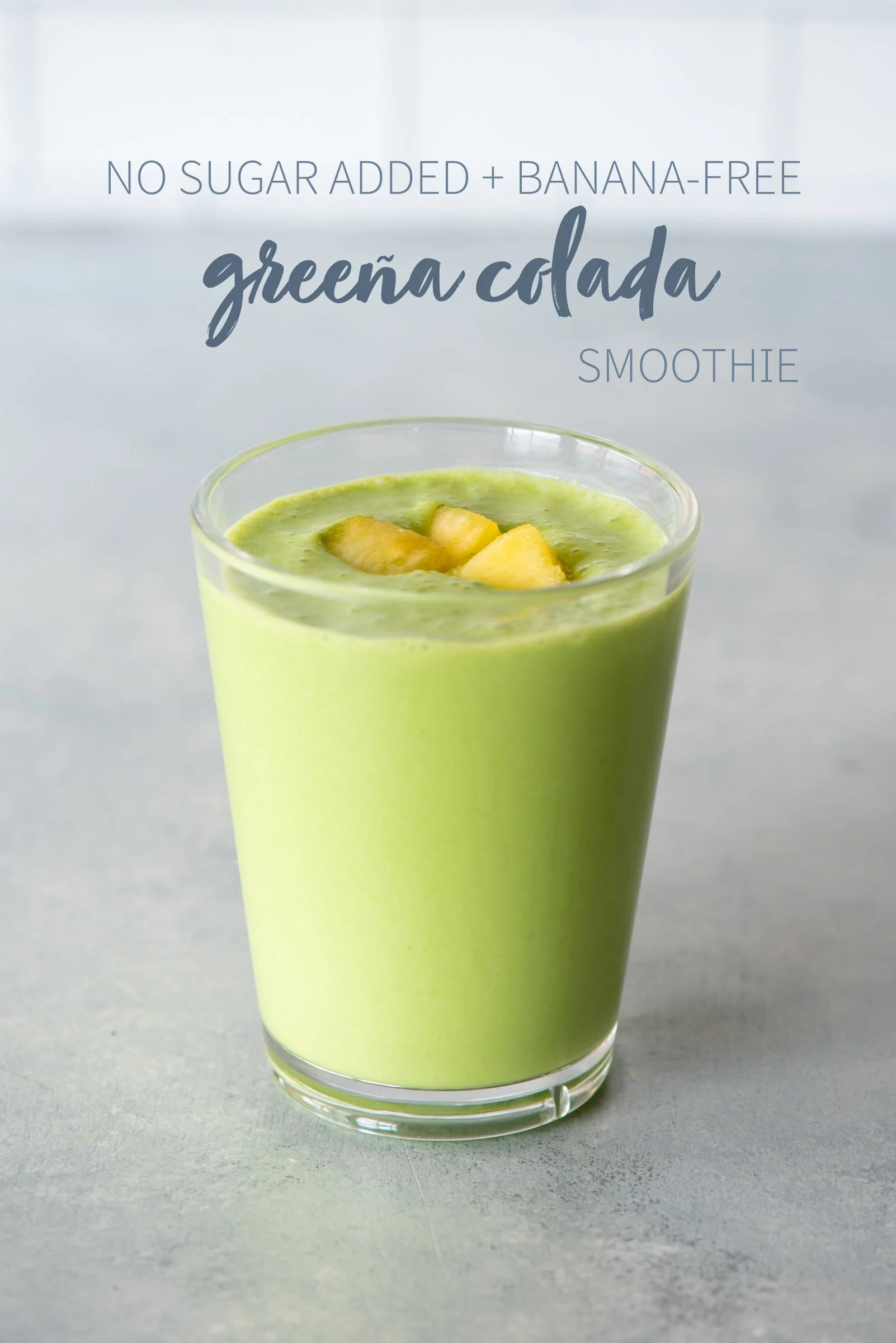 "Greena colada smoothie in a clear glass topped with fruit. A text overlay reads ""No Sugar Added + Banana-Free Greena Colada Smoothie."""