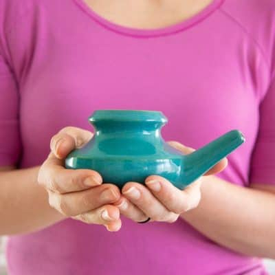 Two hands holding a ceramic neti pot