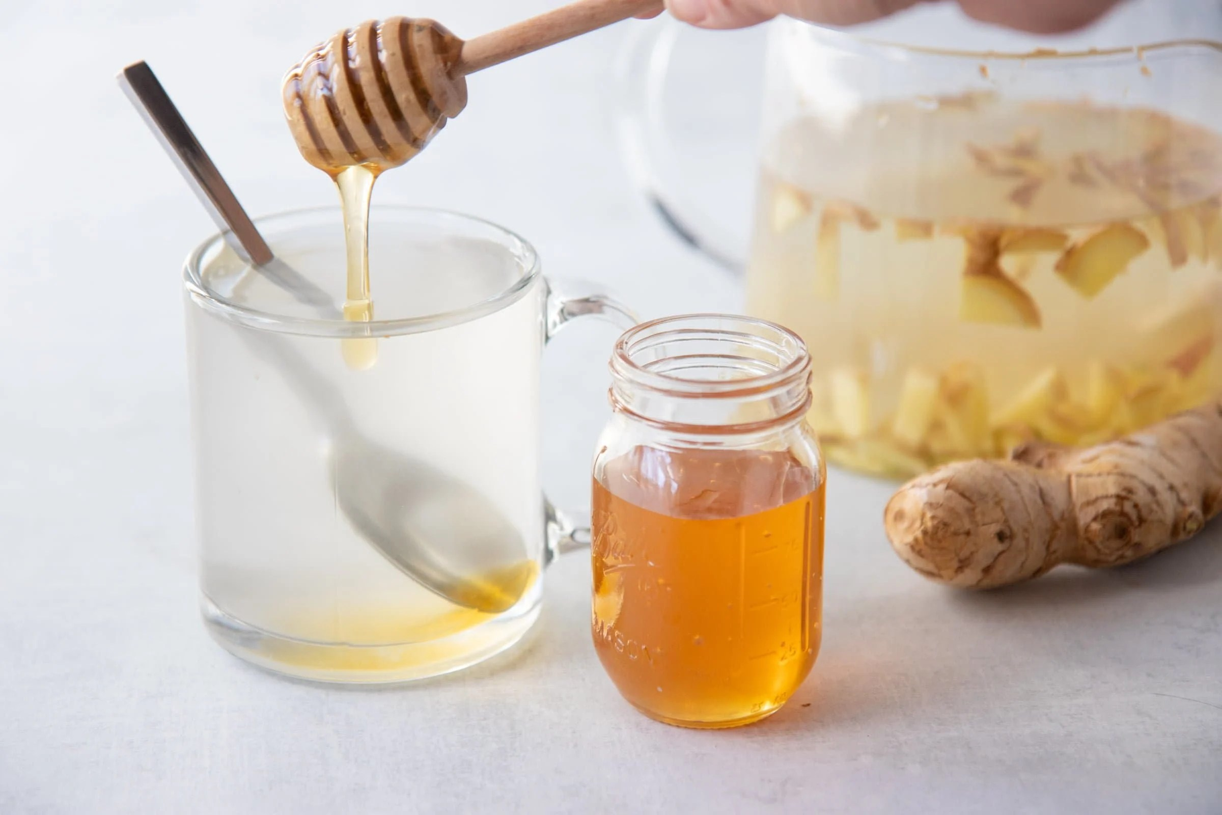 A honey dipper drizzles honey into a clear mug of ginger tea with a jar of honey and pitcher of tea alongside.