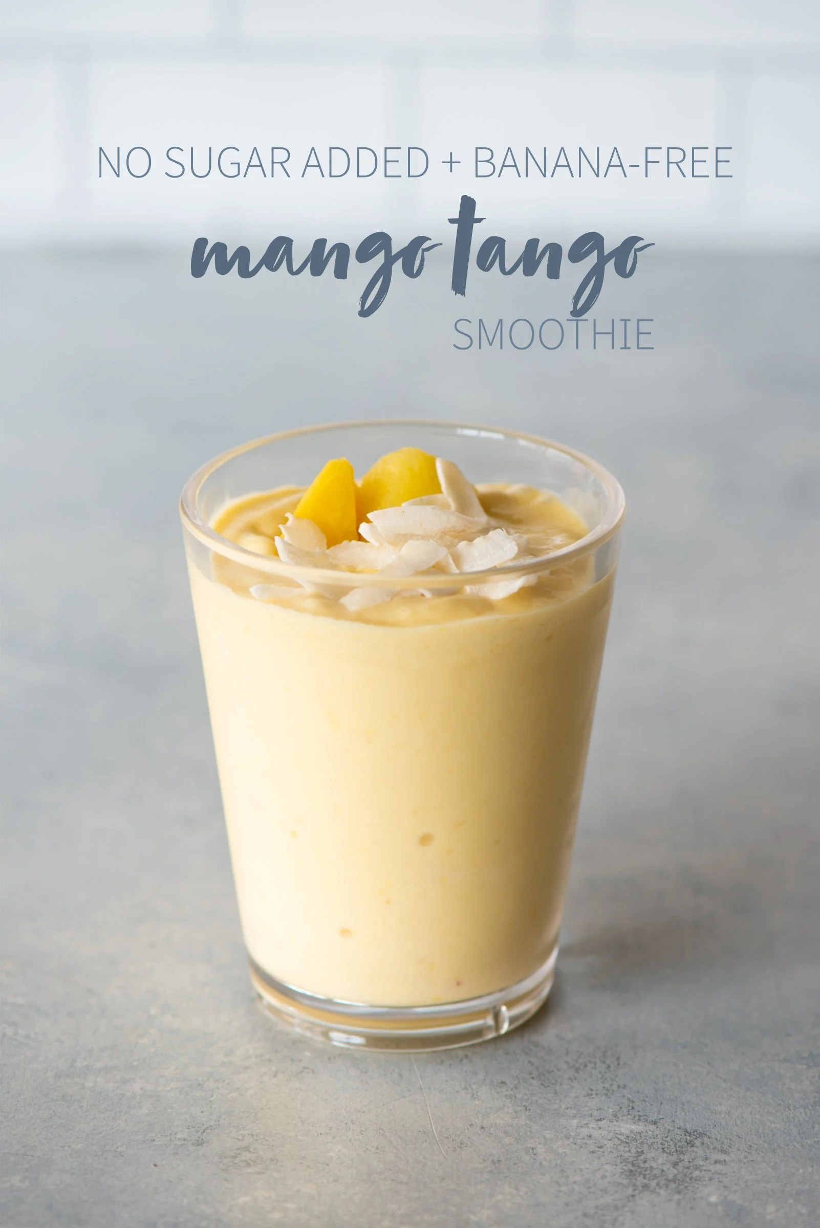 "Mango Tango smoothie in a clear glass topped with mango and coconut. A text overlay reads ""No Sugar Added + Banana-Free Mango Tango Smoothie."""
