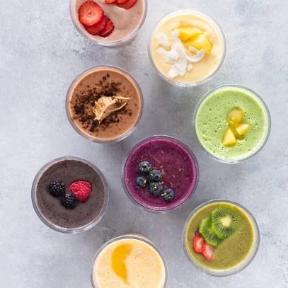 8 Healthy Smoothies Without Banana shown from overhead on a marbled background