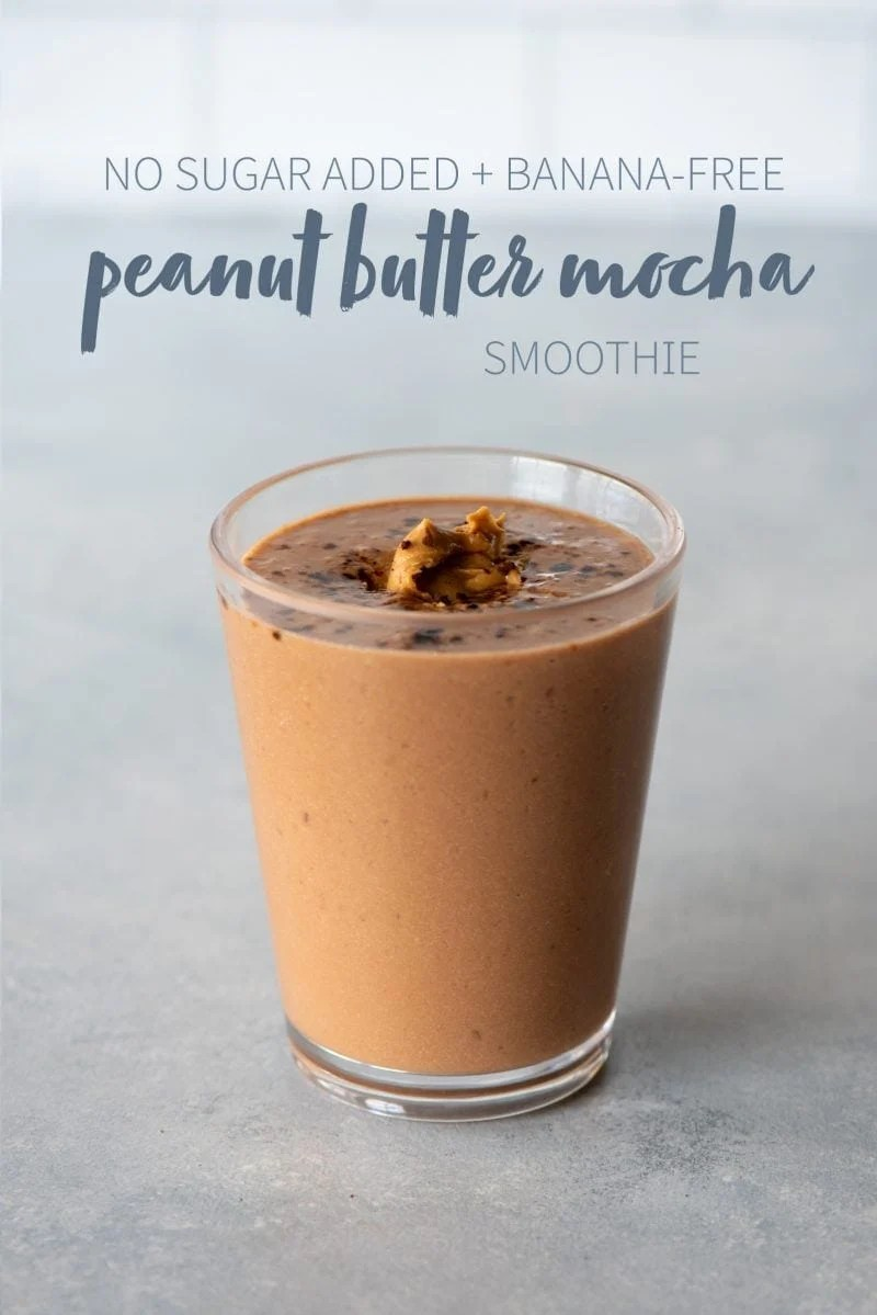 "Peanut butter mocha smoothie in a clear glass topped with peanut butter. A text overlay reads ""No Sugar Added + Banana-Free Peanut Butter Mocha Smoothie."""