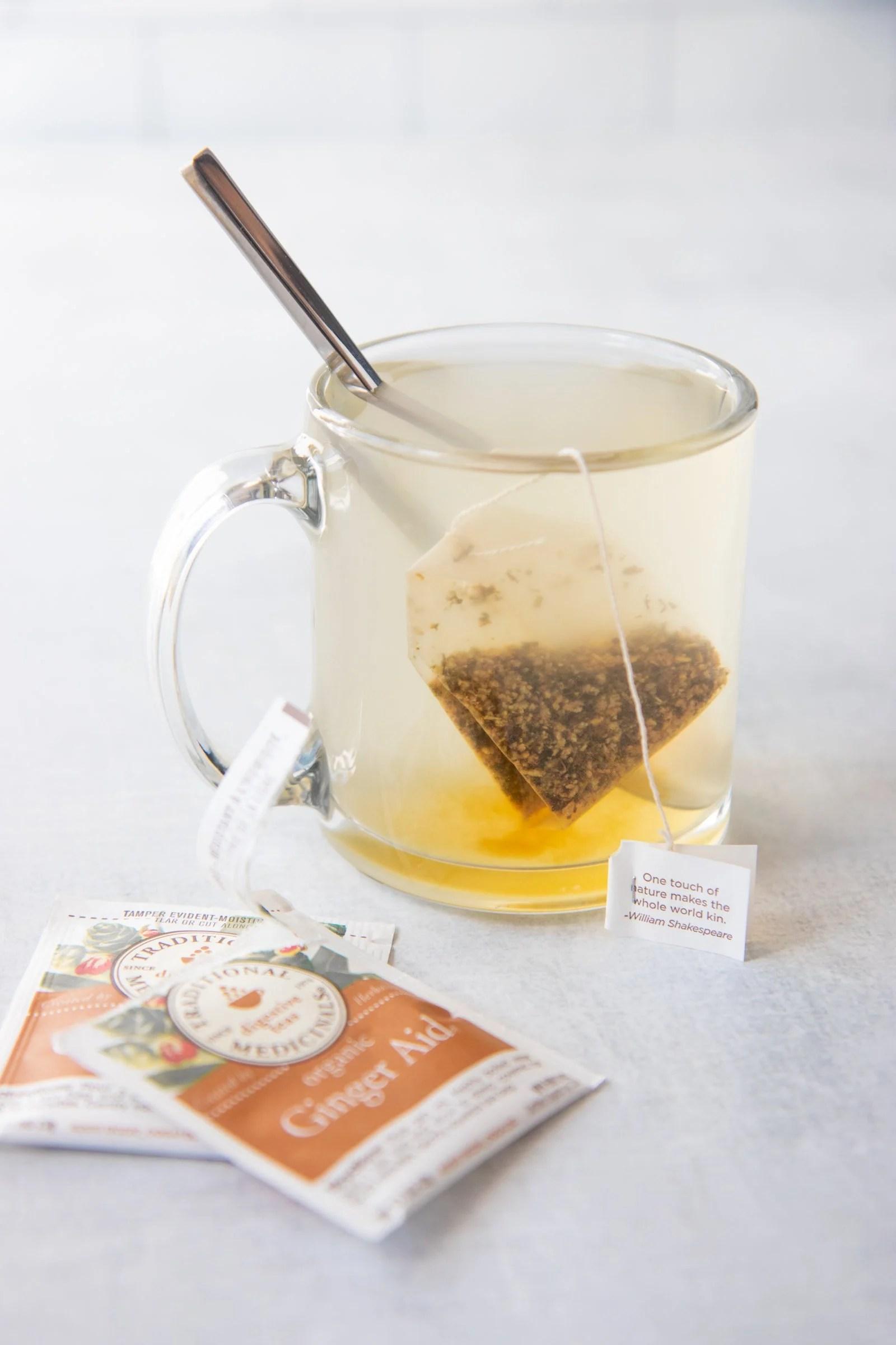 Clear glass mug full of ginger tea with a tea bag in the mug