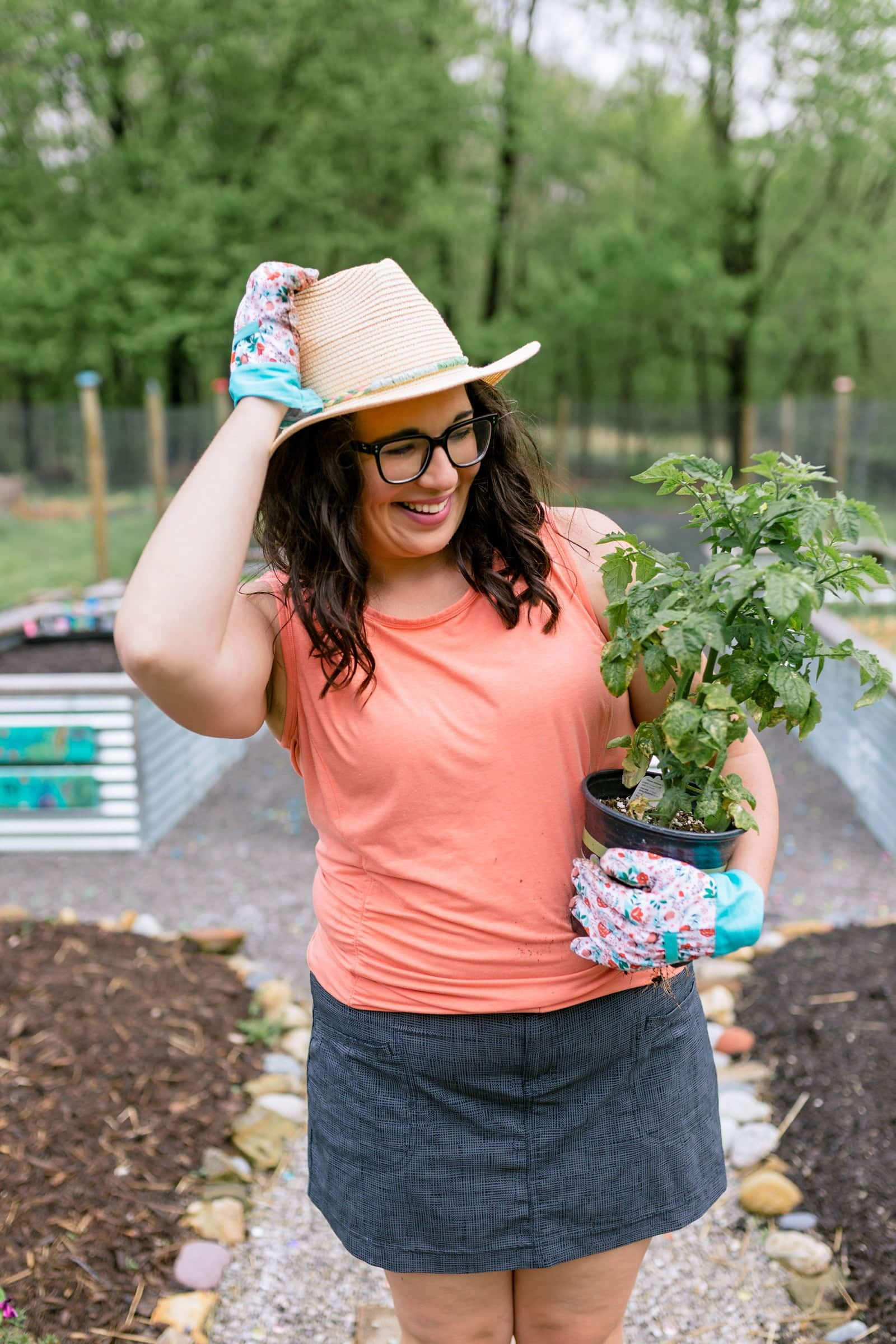Organic Vegetable Gardening for Beginners: Woman in a coral shirt and sun hat smiling and holding a tomato plant ready for planting