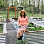 Brunette woman in a coral shirt and a sun hat sitting on the edge of a raised garden bed