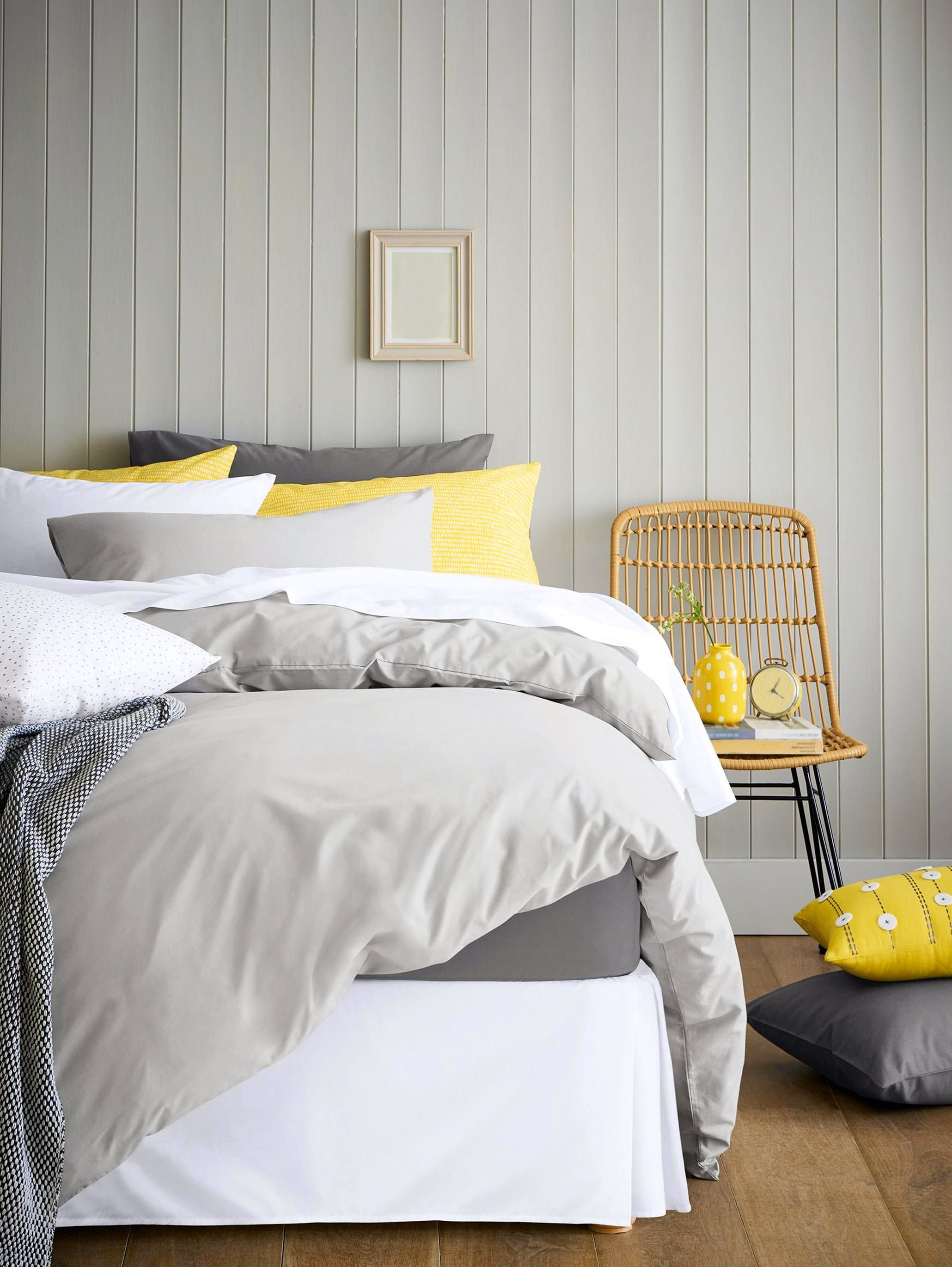 Bed with a grey comforter and white, grey, and yellow pillows.