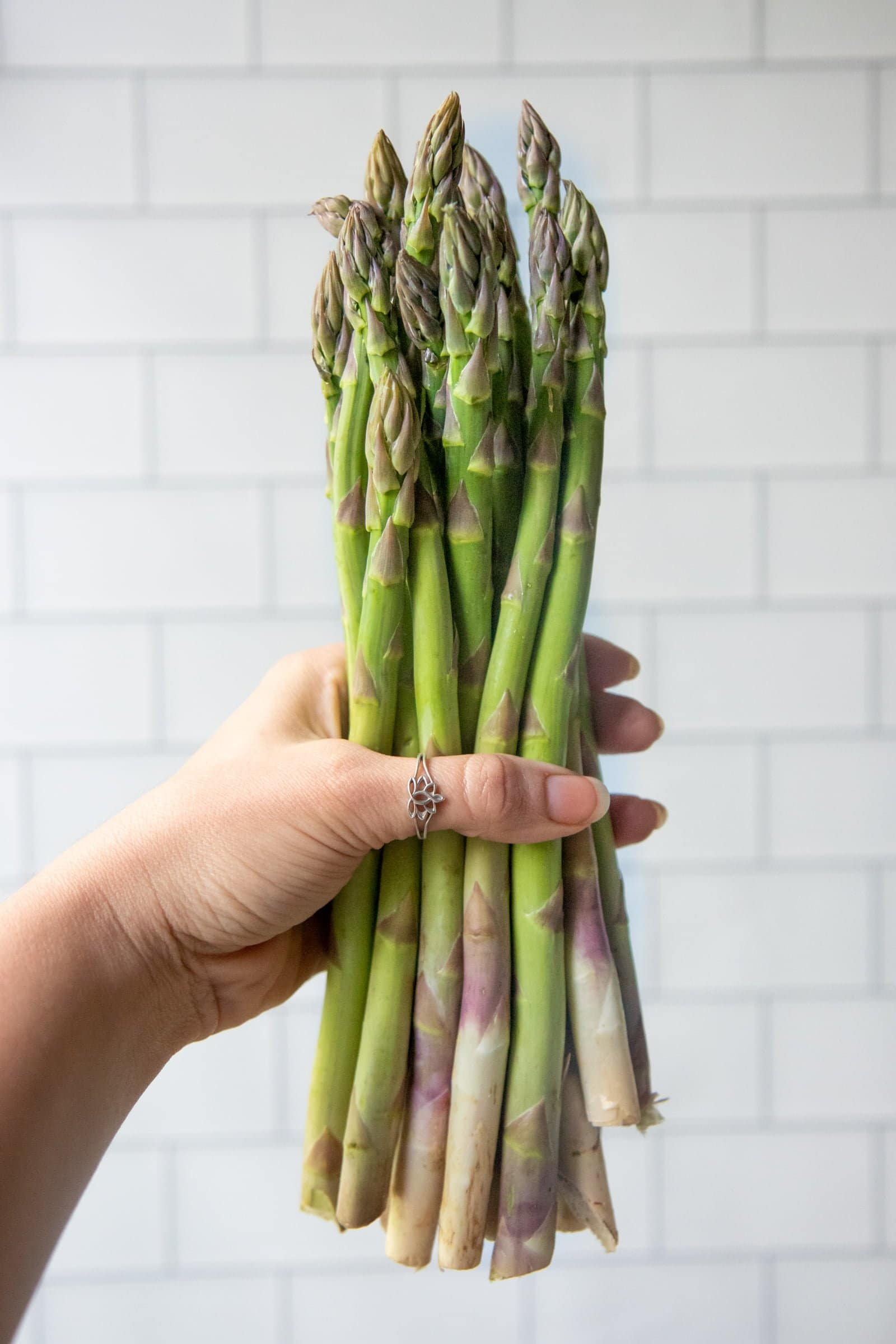 Hand holding a bunch of asparagus spears in front of a white tile background.