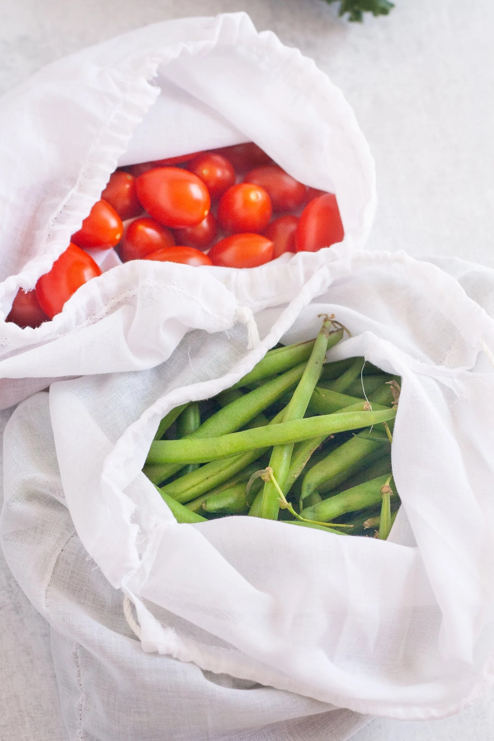 Two white cotton voile drawstring bags, open to show their contents. One holds green beans, the other contains cherry tomatoes.