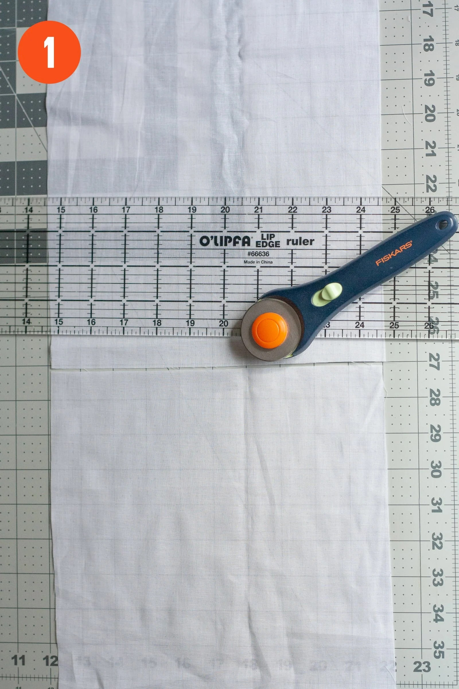 "Rotary cutter and ruler on top of a cut piece of cotton voile. Labeled with a ""1"""