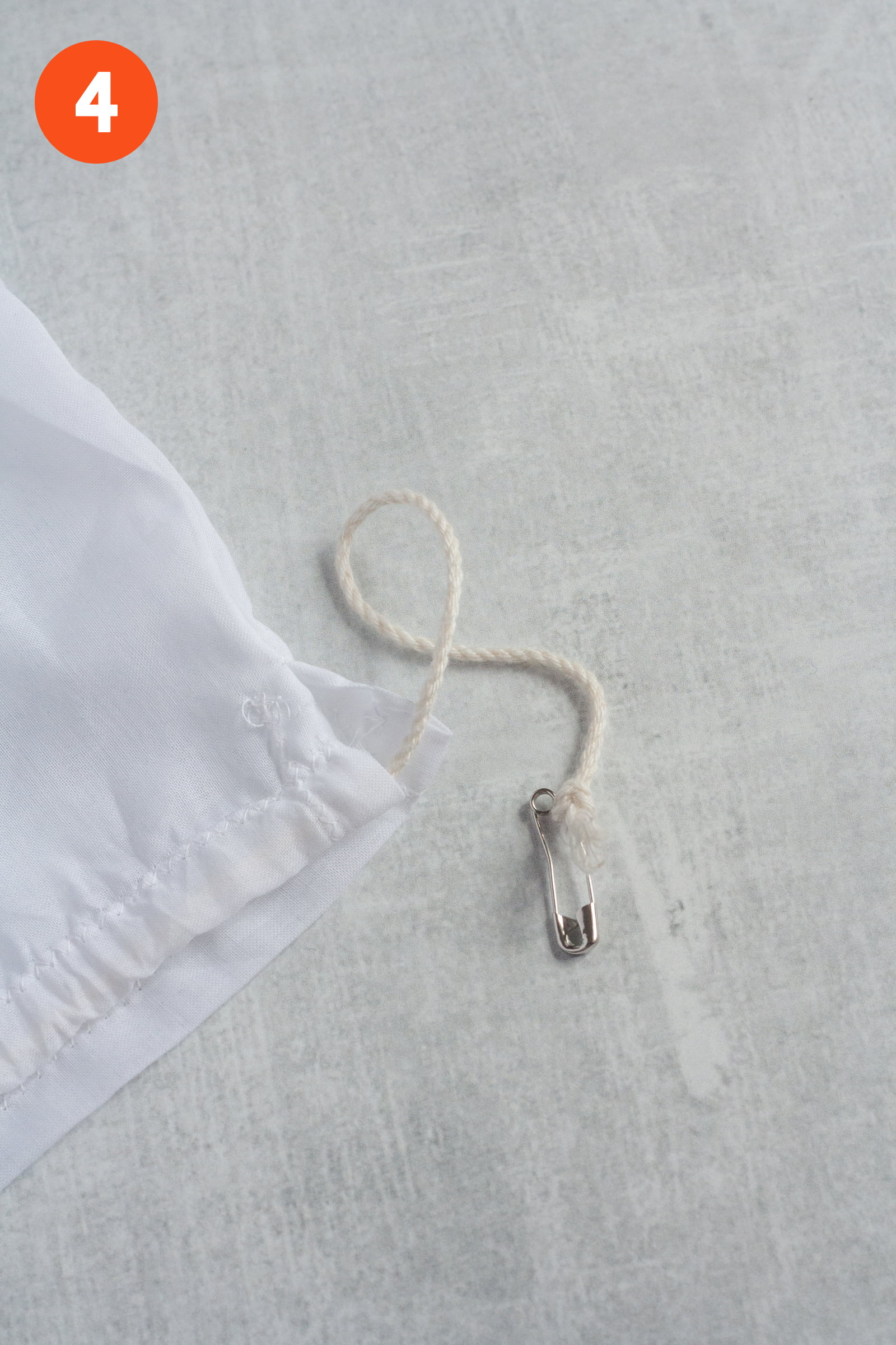 Safety pin with cording tied around it, to help thread the drawstring. Labeled with a 4.