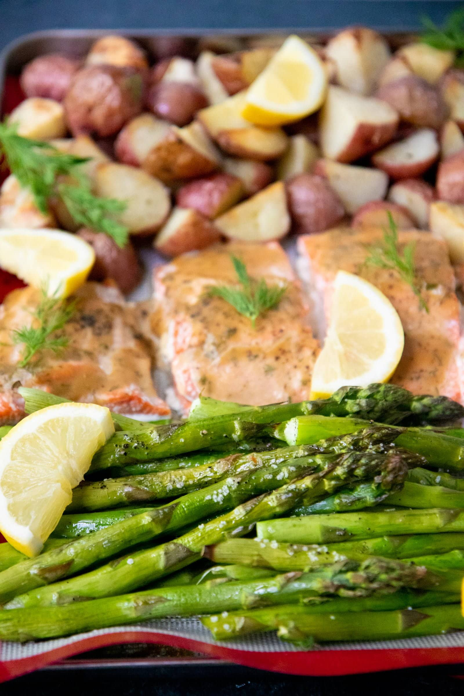 Close-up of roasted asparagus, salmon, and potatoes arranged on a baking sheet with fresh lemon and herbs.