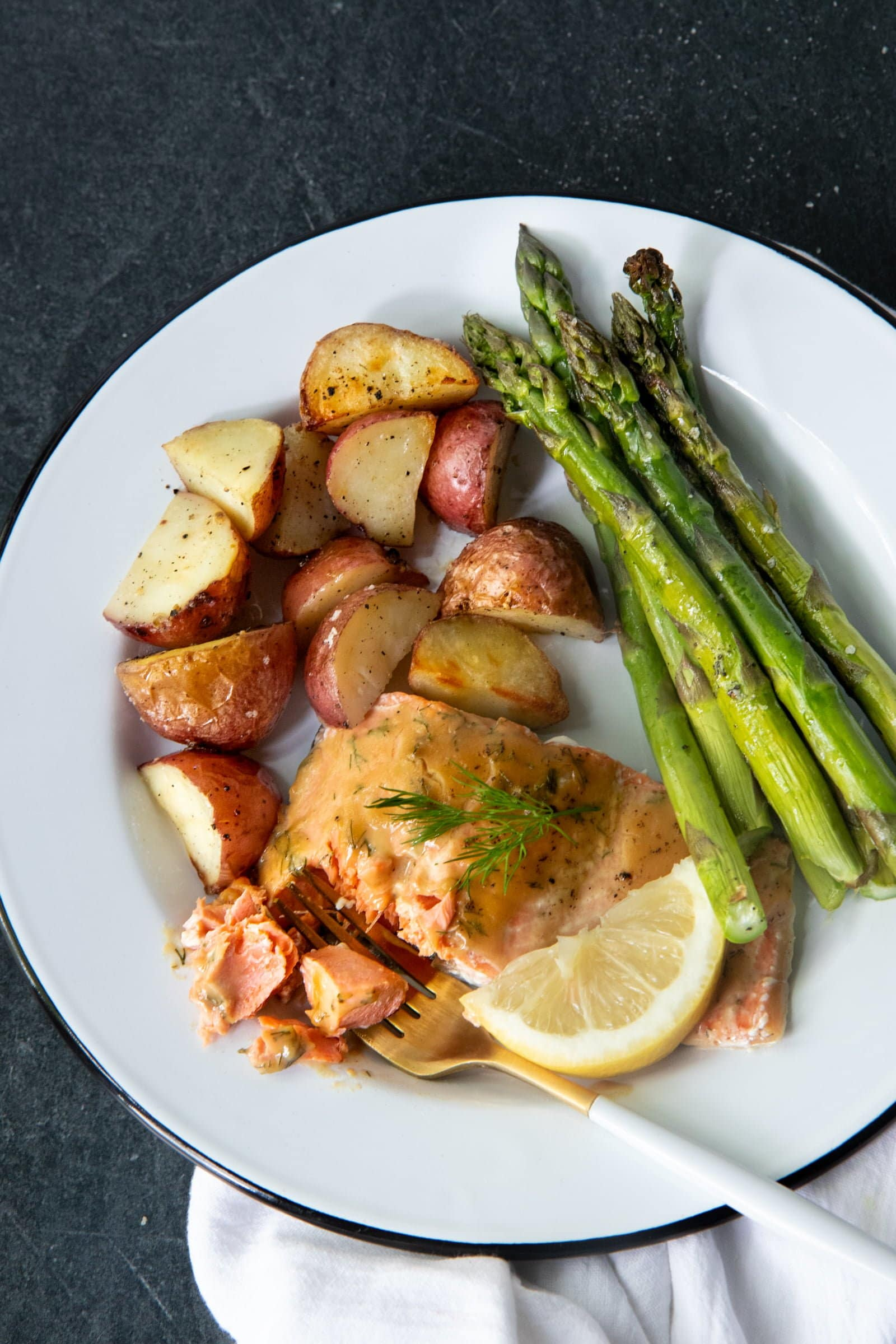 Overhead of roasted maple glazed salmon, asparagus, and potatoes on a white plate with a fork.