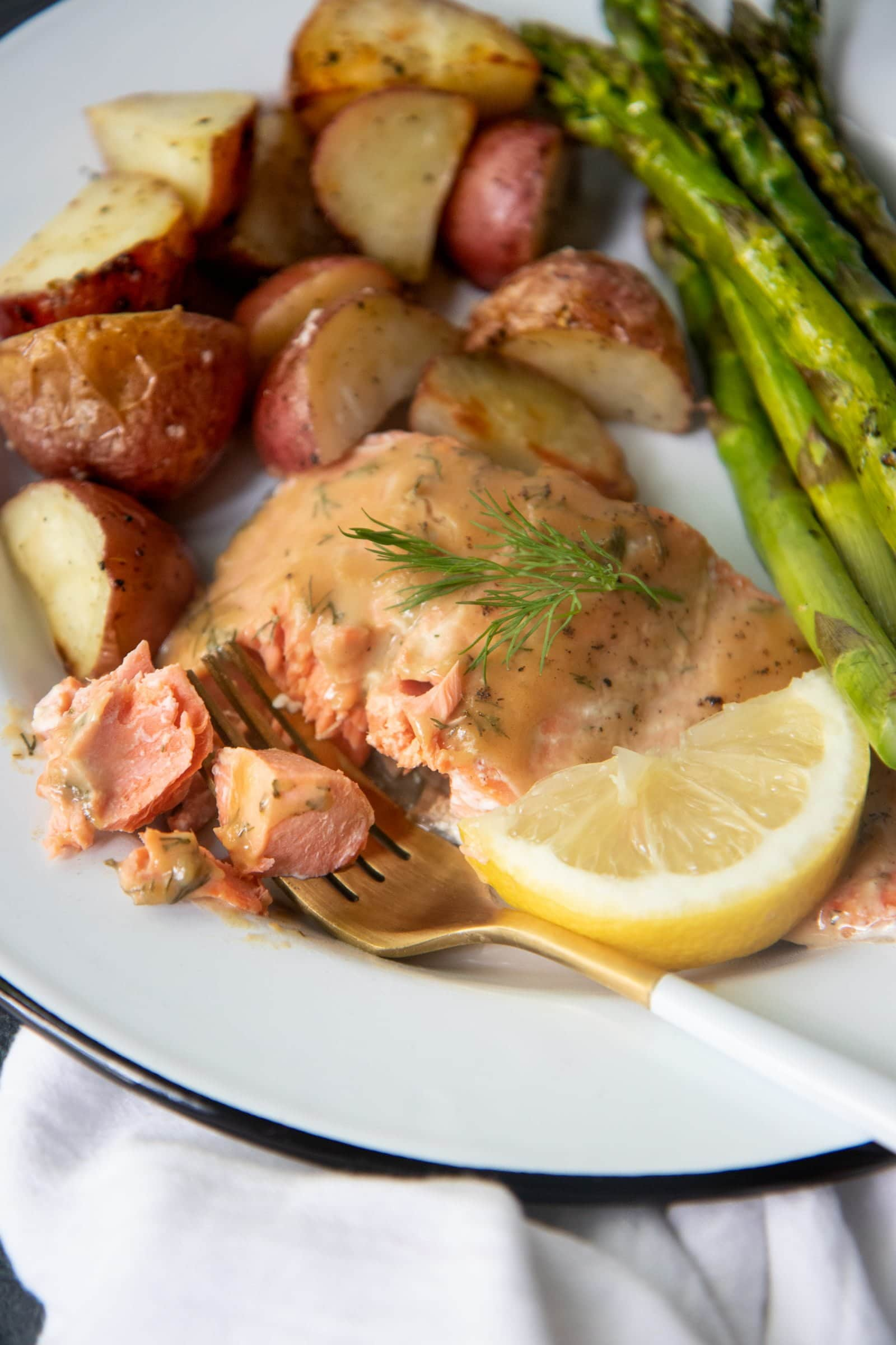 Close-up of roasted maple glazed salmon, asparagus, and potatoes on a white plate with a white and gold fork.
