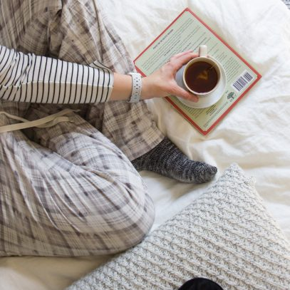 Woman in plaid pajama pants sitting on a bed with a book and mug of tea.