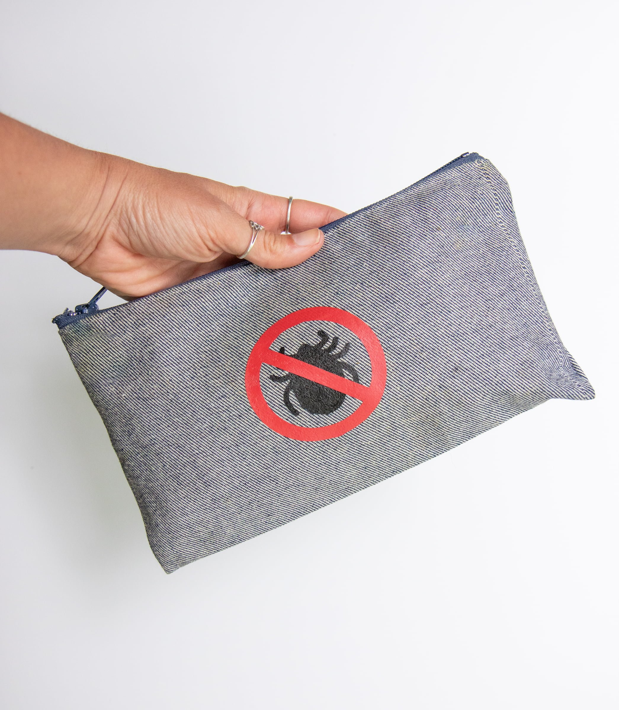 "Hand holding a gray pouch with a ""no ticks"" label. The pouch contains a tick kit - everything you need to deal with a tick bite."