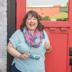 Woman with curly hair in a blue top and a scarf, laughing in front of a red door.