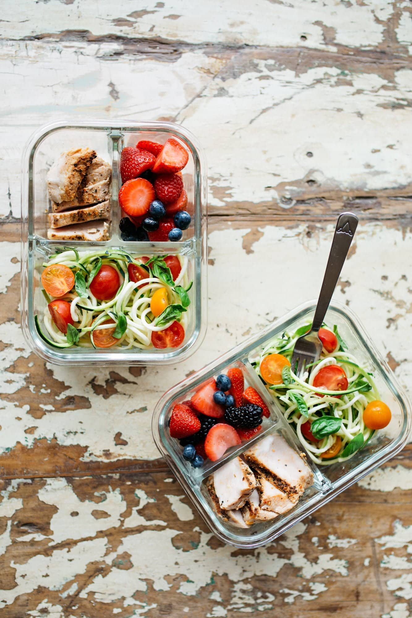 Two divided glass containers filled with a meal prep lunch - chicken, berries, and vegetables.