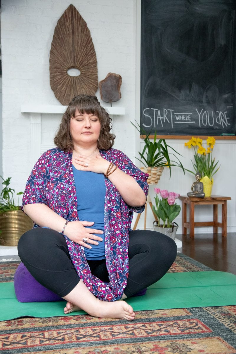 Brunette woman sitting cross-legged on a yoga mat with her eyes closed. One hand is on her stomach and one is on her chest, as she starts meditating.