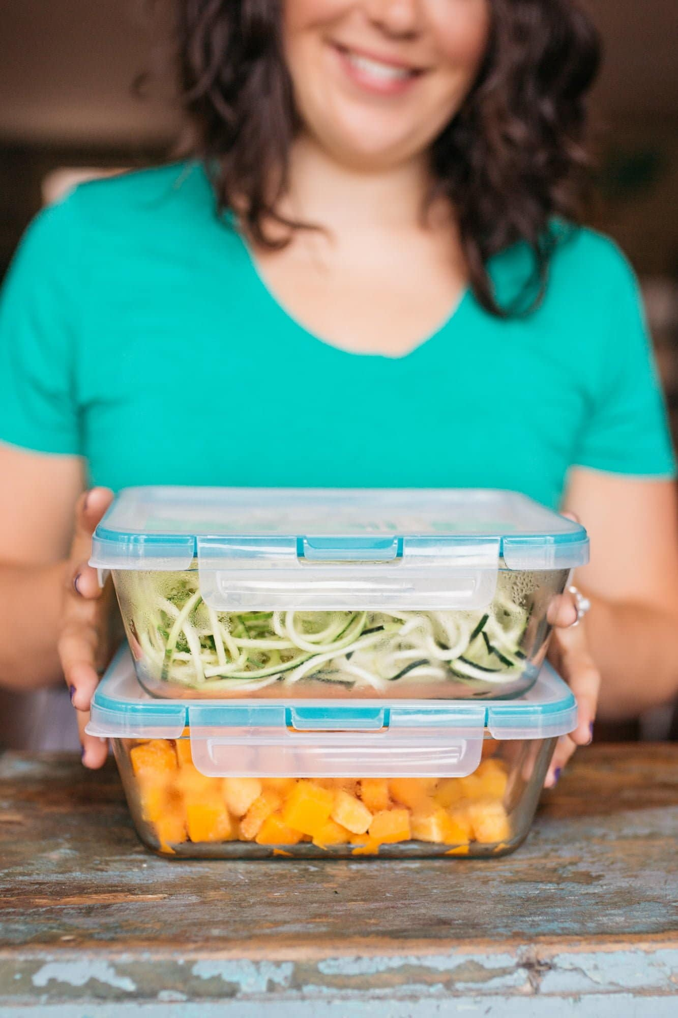 Close-up of a woman holding glass containers. One is filled with zucchini noodles, and the other with sweet potato cubes.