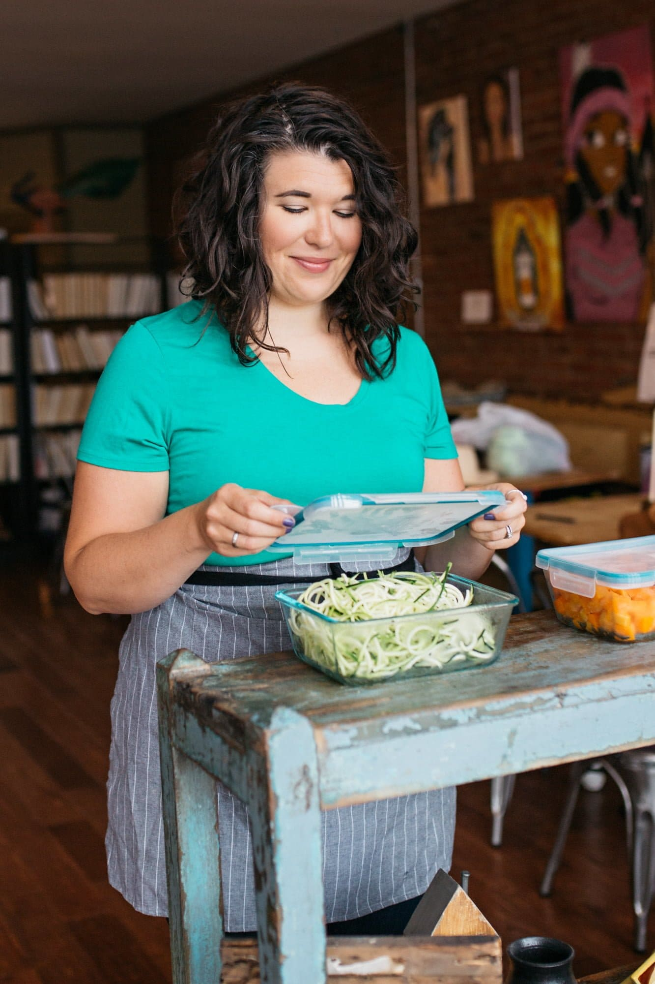 Brunette woman in a teal shirt putting the lid on a glass container filled with zucchini noodles.