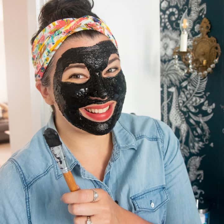 Woman with an activated charcoal face mask on, holding a makeup brush and smiling.
