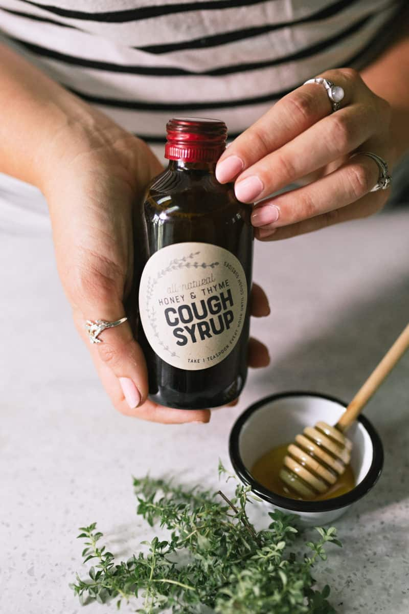 Hands holding a labeled bottle of Honey and Thyme Herbal Homemade Cough Syrup.