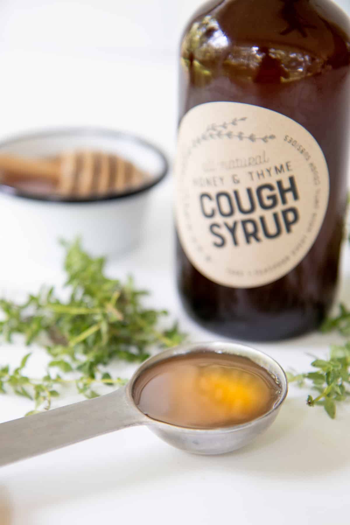 Measuring spoon full of Honey and Thyme Herbal Homemade Cough Syrup in front of a bottle of the syrup.