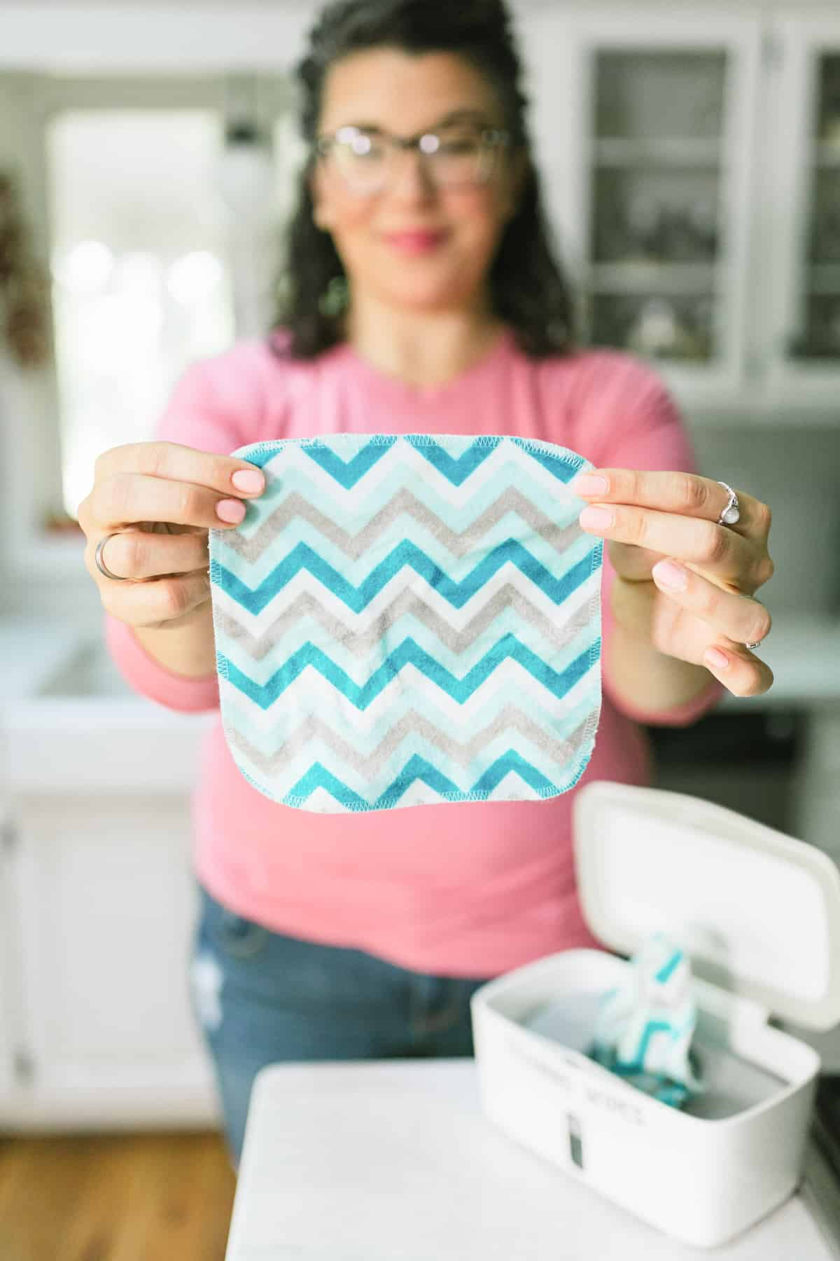 Woman in a pink shirt holding out a square flannel wipe to use as a cleaning wipe
